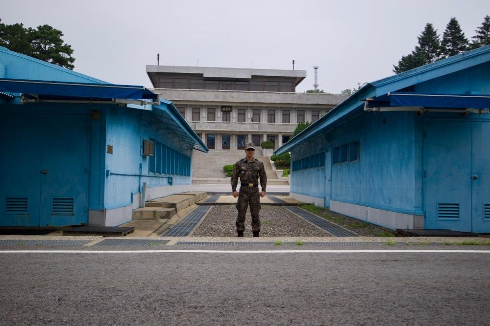Foto der Joint Security Area mit einem US Soldaten zwischen zwei blauen Gebäuden vor der Grenze zu Nordkorea.