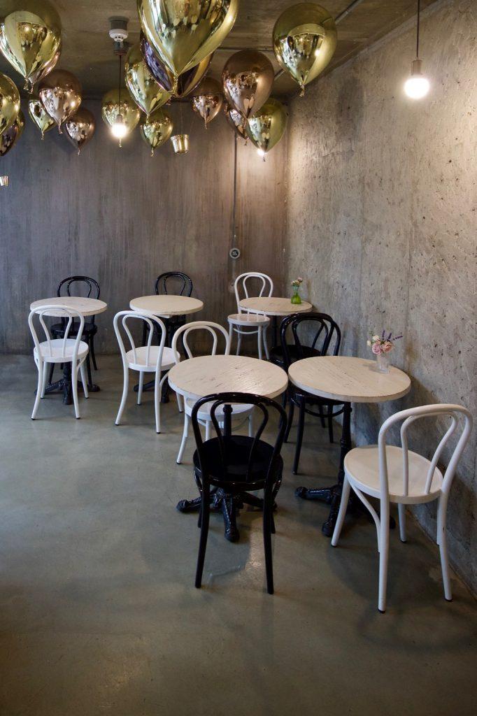 Sitzecke mit Stühlen und goldenen Luftballons an der Decke